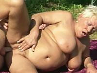 Naakt zonnende sloerie krijgt de lul van haar buurjongen in haar mond gehangen.