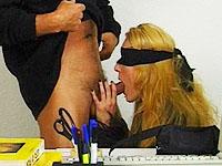 Lekker blond wijf laat zich achter het bureau neuken door een collega van haar.
