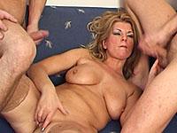 Rijpe vrouw laat twee jonge maagden met haar lichaam experimenteren.